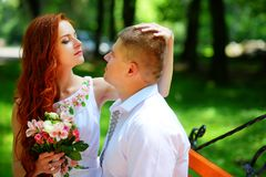 Bruden och brudgummen sitter på en bänk arkivfoton
