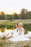 Bruden och brudgummen sitter vid sjön och ser solnedgången Arkivbilder