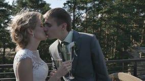 Bruden och brudgummen som dricker champagneanseende på verandan av sommarkafét arkivfilmer