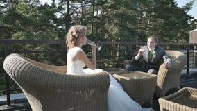 Bruden och brudgummen som dricker champagnesammanträde på verandan, sommarkafé, Steadicam arkivfilmer