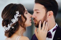 Bruden och brudgummen som kramar och kysser Nygifta personer royaltyfria foton