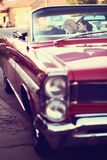 Bruden och brudgummen som kysser och, har gyckel bak hjulet av den röda retro tappningbilen bröllop Royaltyfria Foton