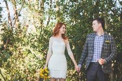 Bruden och brudgummen som poserar i skogen Fotografering för Bildbyråer