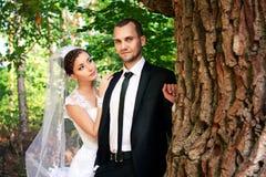 Bruden och brudgummen som in poserar, parkerar Royaltyfri Foto
