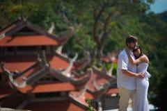 Bruden och brudgummen står på bakgrunden av den gamla kinesiska templet royaltyfri foto