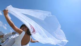 Bruden och brudgummen står på en stark vind på bröllopdagen nära havet Skyla brudar som fladdrar beautifully i vinden stock video