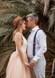 Bruden och brudgummen står och rymmer händer på bakgrund av palmträd Arkivfoto