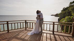 Bruden och brudgummen tillsammans på en hög balkong som förbiser havet och reverna Sinnlig omfamning av förälskelse, lycka och stock video