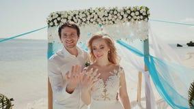 Bruden och brudgummen visar av vigselringar arkivfilmer