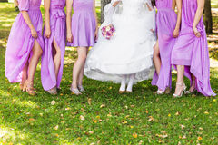 Bruden och brudtärnor visar av deras skor på bröllop royaltyfri bild