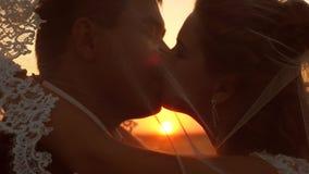 Bruden och den brudgumkyssen och kramen p? solnedg?ngen N?rbild f?r?lskat kyssa f?r romantiska par p? solnedg?ngen Begreppet av e lager videofilmer