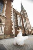 Bruden på går nära väggen av den gamla gotiska kyrkan arkivfoton