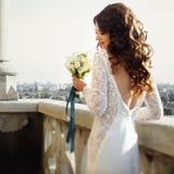 Bruden poserar tillbaka med liljabuketten med cityscape på bakgrunden Royaltyfri Foto