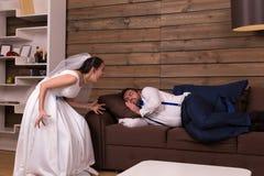 Bruden ropar på att sova på soffabrudgum Royaltyfria Bilder