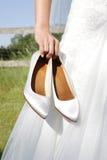 Bruden rymmer brud- skor i hand Royaltyfri Bild