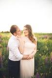 Bruden rymmer brudgummens hals, medan han kysser henne i strålarna av solnedgången Royaltyfri Fotografi