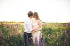 Bruden rymmer brudgummens hals, medan han kysser henne i strålarna av solnedgången Arkivbild