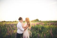 Bruden rymmer brudgummens hals, medan han kysser henne i strålarna av solnedgången Arkivfoton
