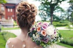 Bruden rymmer en bröllopbukett, bröllopsklänningen, bröllopdetaljer Begrepp för bröllopceremoni Arkivfoton
