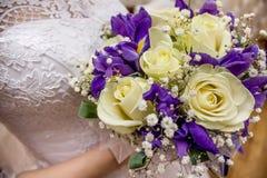 Bruden rymmer en bröllopbukett och ett exponeringsglas av champagne Arkivfoto
