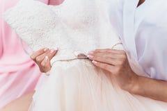 Bruden rymmer en bröllopsklänning Royaltyfri Bild