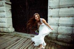 Bruden rymmer hennes klänning, medan vind blåser den bort Arkivbilder