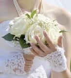 Bruden rymmer vita rosor i hennes hand Härliga vita fragmen arkivfoto