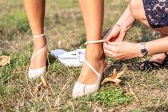 Bruden sätter på att gifta sig skor på hennes mjuka fot med hennes förnämsta brudtärna Arkivbilder