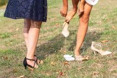 Bruden sätter på att gifta sig skor på hennes mjuka fot med hennes förnämsta brudtärna Royaltyfri Foto