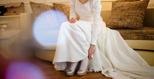 Bruden sätter på hennes skor Royaltyfri Fotografi