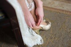 Bruden sätter på vita skor för att gifta sig arkivbild