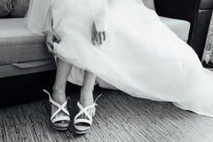 Bruden sätter på vita skor på fot arkivfoton