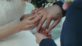Bruden sätter vigselringen på brudgummens finger Bröllopceremoni nära vattnet Förbindelsehänder med cirklar tätt lager videofilmer