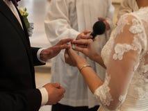 Bruden sätter vigselringen på fingret för brudgum` s under ceremonin i kyrka under övervakningen av prästen, tjecktekniker Royaltyfri Bild