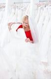 Bruden ser framåtriktat för att försöka på klänningen Arkivfoton