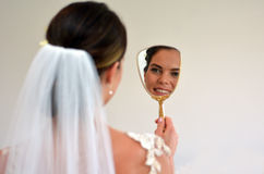 Bruden ser henne i spegeln på hennes bröllopdag Royaltyfri Bild