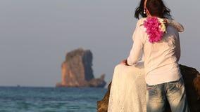 Bruden sitter vaggar på, och brudgummen kommer och kysser på soluppgång lager videofilmer