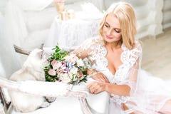Bruden snör åt in med bröllopsminket som smilingly ser royaltyfri fotografi