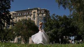Bruden som dansar parkera på hennes bröllopdag Flickan i en vit klänning med ett drev, körningar till och med parkera arkivfilmer