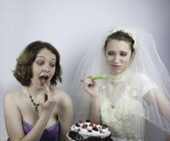 Bruden som försöker att banta, frestas av brudtärnan Arkivfoto