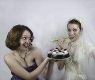 Bruden som försöker att banta, frestas av brudtärnan Arkivfoton