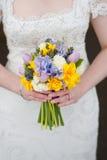 Bruden som rymmer en bröllopbukett av våren, blommar Royaltyfri Bild