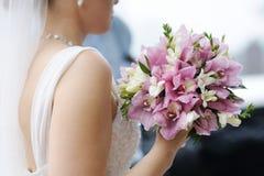 Bruden som rymmer härligt bröllop, blommar buketten Arkivbilder