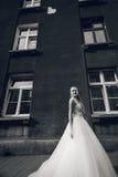 Bruden står framme av byggnaden fotografering för bildbyråer