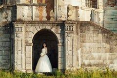 Bruden står i bågen av slotten som skins av soliga strålar Royaltyfri Fotografi