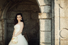 Bruden står i bågen av slottväggen Arkivfoto