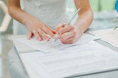 Bruden undertecknar förbindelsebesiktningsinstrumenten parförlagor som undertecknar bröllopbarn Fotografering för Bildbyråer
