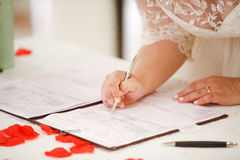 Bruden undertecknar vigselbeviset Royaltyfria Foton