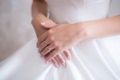Bruden vek hennes händer på klänningen Arkivbilder
