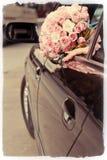 Bruden visar bröllopbuketten från fönster av bilen Royaltyfri Foto
